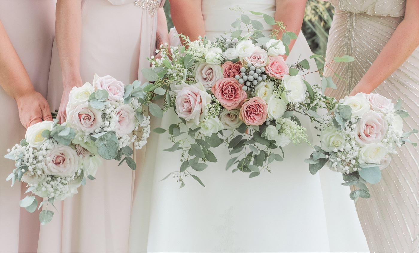 Bride and bridesmaids hold wedding flower bouquets made from pink roses, eucalyptus and white flowers