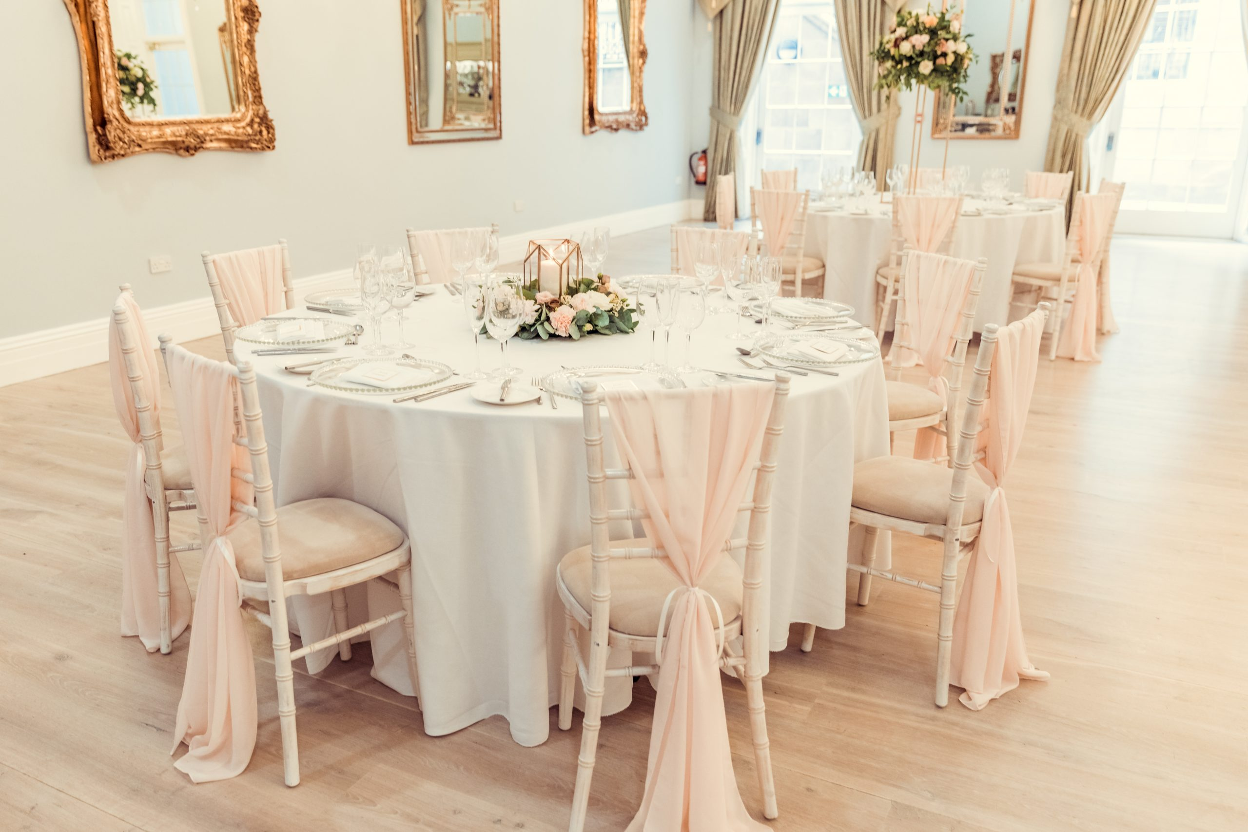 A table decorated for a wedding at Doxford Hall with blush pink chair sashes and a gold lantern centrepiece with flowers