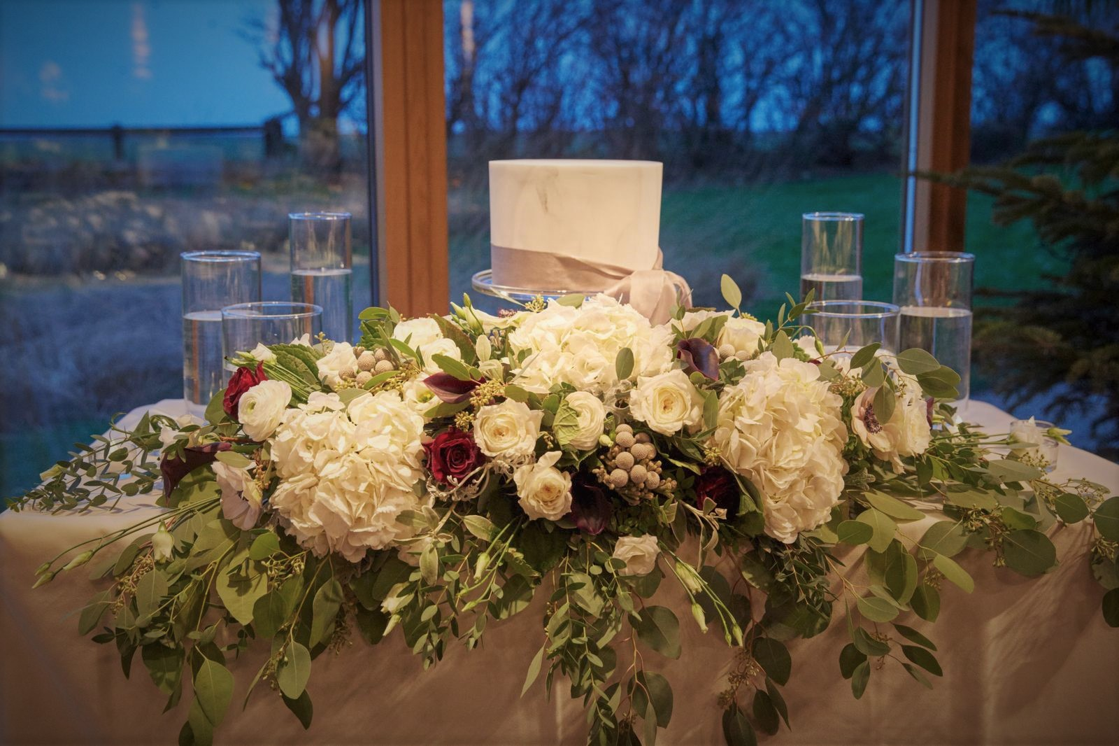 Wedding flowers and a wedding cake at Newton Hall in Northumberland