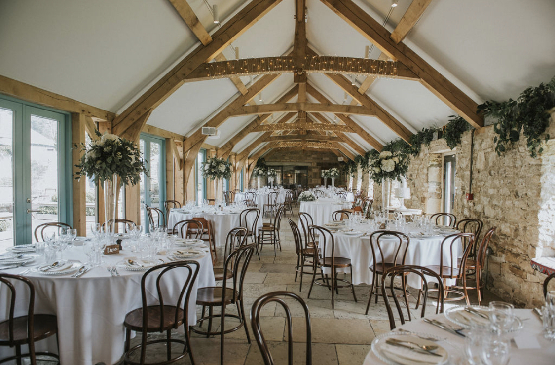 Healey Barn dining room dressed for a wedding with wedding centrepieces