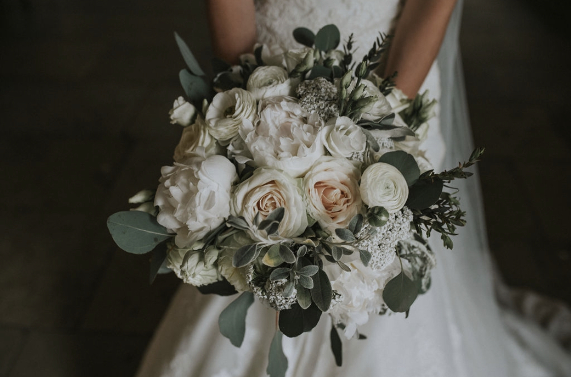 A luxury bridal wedding bouquet of white and blush flowers with eucalyptus foliage