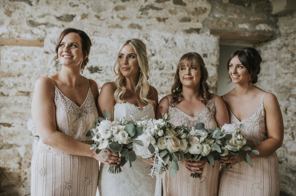 A bride and her bridesmaids at Healey Barn in Northumberland, holding bouquets of luxury wedding flowers