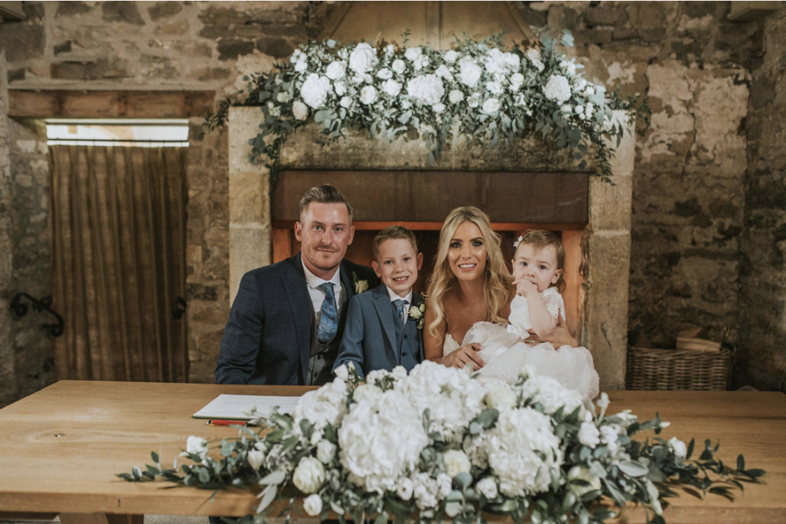 Bride, Groom and their children infront of the fireplace at Healey Barn. The fireplace is decorated with a large floral arrangement and there is an arrangement of wedding flowers on the table in front of them.